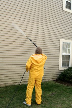 Pressure washing the siding of a house by Rubio's Painting Services.